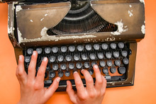 A Old Typewriter With Hands An...