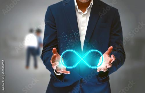 Fotografie, Obraz DevOps concept, IT engineer holding the glowing Devops symbol that illustrates t