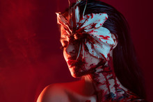 Blood Lily, Scary And Sexy Halloween Look. Beautiful Young Brunette Girl On Red Background.