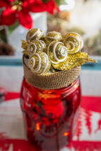 DIY Christmas Decorated Red Jar With Burlap Wrapped Lid, And Gold Glittery Balls Glued To The Lide