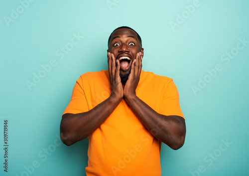 Amazed and shocked expression of a boy over cyan background Fototapet
