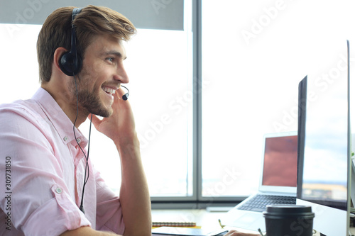 Photo Happy young male customer support executive working in office.