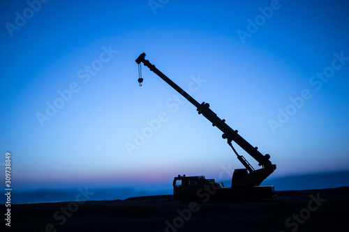 фотография Abstract Industrial background with construction crane silhouette over amazing sunset sky