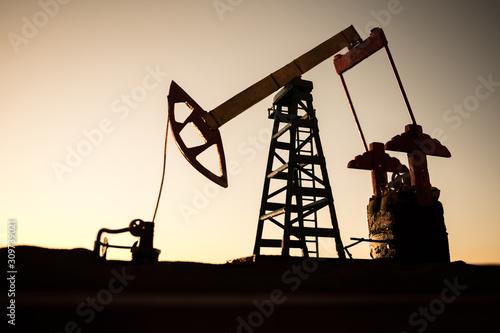 Fototapeta Creative artwork decoration. Oil pump and oil refining factory at sunset. Energy industrial concept. Selective focus. obraz