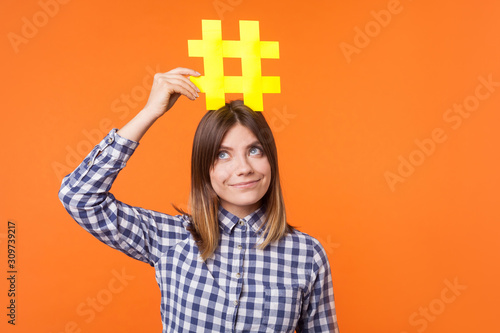 Popularity in social media. Portrait of funny brunette woman wearing checkered casual shirt holding large big yellow hashtag sign on head as crown. indoor studio shot isolated on orange background