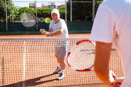 Fotografie, Obraz  mature sportsman playing at tennis court