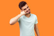 canvas print picture - Call me! Portrait of happy playful brunette man with beard in white t-shirt making gesture with fingers dial my number or call me back and flirting. indoor studio shot isolated on orange background