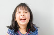 canvas print picture - Happy Little asian girl child showing front teeth with big smile and laughing: Healthy happy funny smiling face young adorable lovely female kid.Joyful portrait of asian elementary school student.
