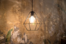 Industrial Style Wire Lamps With Filaments Glowing Inside Glass Light Bulbs In Darkness. Shiny Lights And Dark Background. Urban Style Interior Lighting With Cage Lampshades. Grunge Decoration.