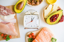 Intermittent Fasting And Healthy Food. Concept.Alarm Clock And Keto Diet Food Ingredients On White Table.Ketogenic Mean Low Carb And High Fat.