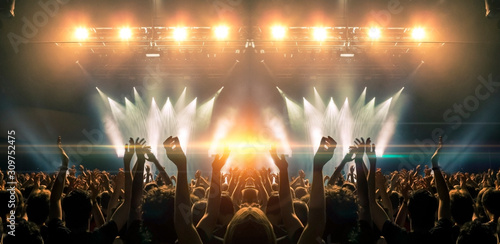 Photo of a concert hall with people silhouettes clapping in front of a big stage lit by spotlights. Shot is taken from concert crowd point of view, lens flare is visible. - 309752475