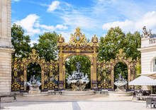 The Fountain Of Neptune In The Rococo Style And The Gilded Wrought Iron Portico In The North-west Corner Of The Place Stanislas In Nancy, France.