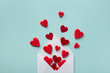 canvas print picture - Valentine day greeting concept. Envelope and red hearts on blue background top view. Flat lay.