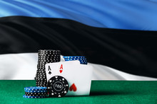 Estonia Casino Theme. Two Ace In Poker Game, Cards And Black Chips On Green Table With National Flag Background. Gambling And Betting.