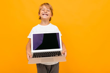 European Boy Holds Laptop Screen Forward With Mockup On Orange Studio Background With Copy Space
