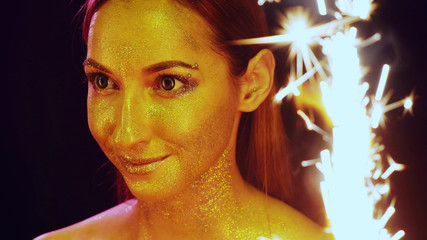 portrait of a girl with glitter on the face  between the sparklers