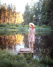 Alone Girl With A Straw Hat Standing Near A Pond Enjoying A Summer Day In The Forest.