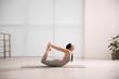 Young woman practicing bow asana in yoga studio. Dhanurasana pose