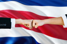 Costa Rica Agreement Concept. Man And Woman Fist Bumping On National Flag To Show Cooperation. Peace And Teamwork Theme.