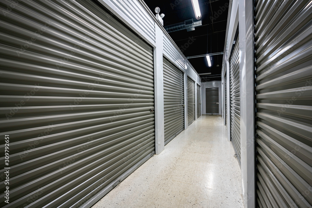 Fototapeta Long storage facility corrodor. Garage doors with light
