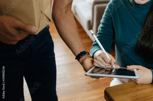 Photo asian woman customer appending signature in digital mobile tablet receive parcel