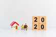 Miniature people, elderly lover sitting with mini house and year 2020 wooden block using as job retirement and family concept