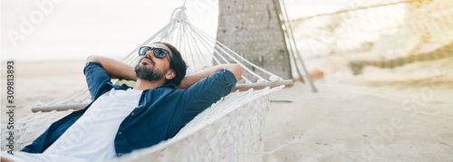 Photo A man enjoys calm, lies in a hammock on the background of the ocean and sunset