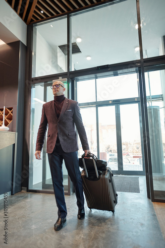 Mature male business traveler pulling suitcase while entering hotel lounge