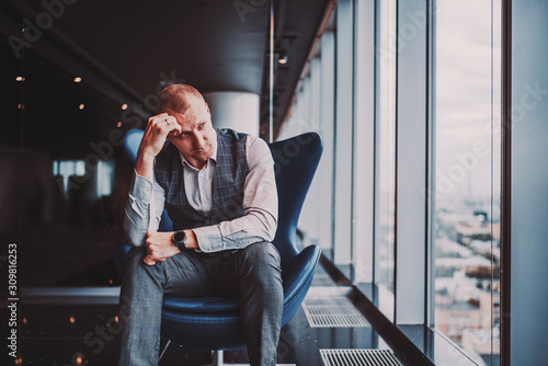Fotografía An annoyed and depressed caucasian man entrepreneur is sitting on an armchair of
