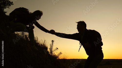 female traveler holds the hand of a male traveler helping to climb top of the hill Canvas Print