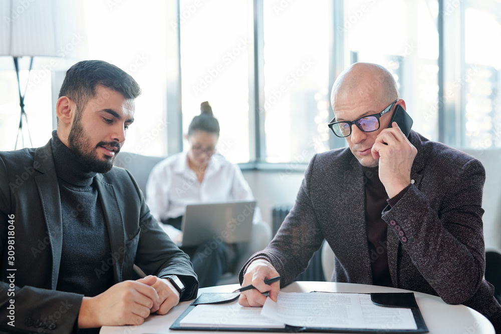 Fototapeta Busy broker in formalwear looking through papers and consulting client by phone