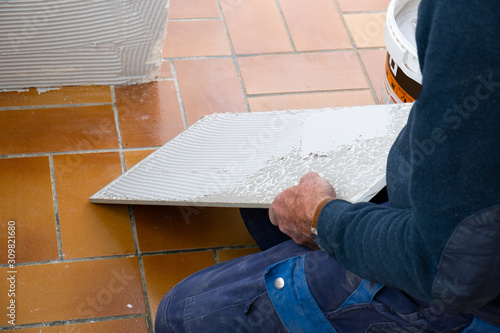 the tiler puts glue on the ceramic tile before laying it Canvas Print