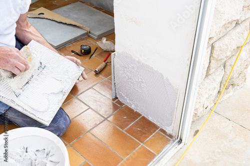 Photo the tiler puts glue on the ceramic tile before laying it