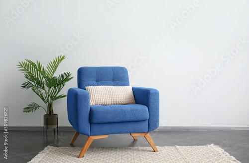 Fototapeta Comfortable blue armchair and houseplant near light wall obraz