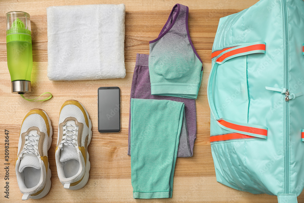 Fototapeta Flat lay composition with sports bag on wooden background
