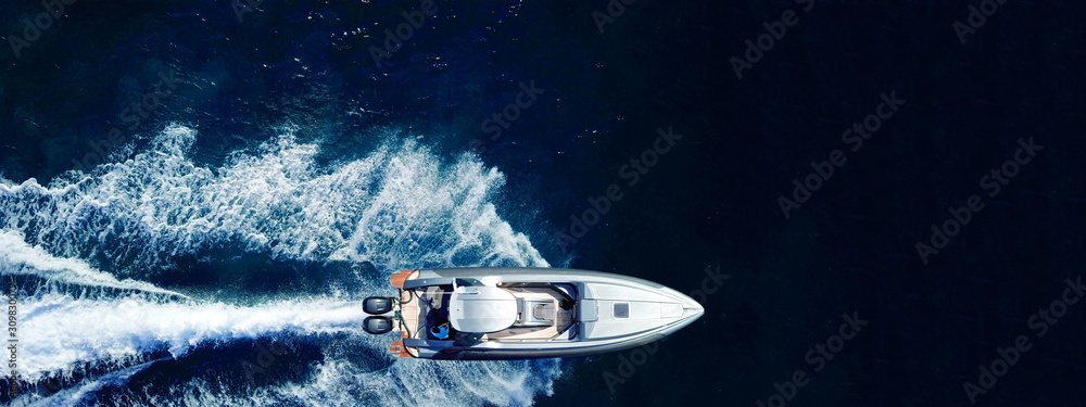 Obraz Aerial drone ultra wide top down photo of luxury rigid inflatable speed boat cruising in high speed in Aegean deep blue sea, Greece fototapeta, plakat