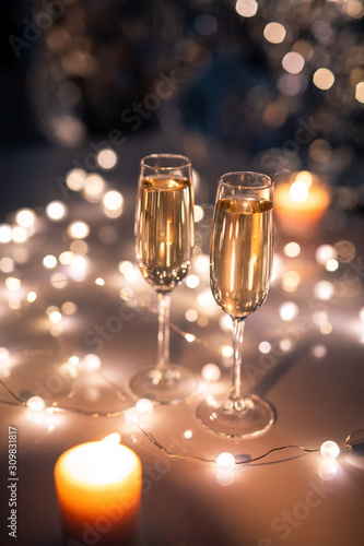Two crystal flutes of champagne surrounded by lit garlands and burning candles - 309831817