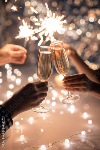 Obraz Hands of friends holding flutes of champagne and sparkling bengal lights - fototapety do salonu