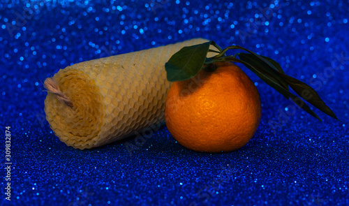 Natural beeswax candle and fresh mandarin on a blue background Organic handicraft object Romantic candle made for the holiday Wallpaper Mural