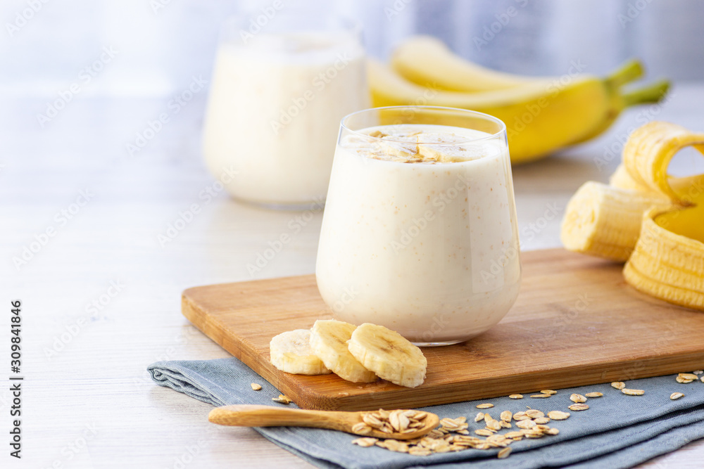 Fototapeta Vegan banana and oatmeal smoothie in glass jar on the light background. Healthy food.