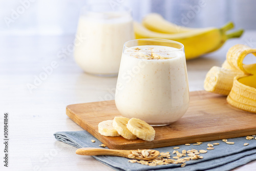 Foto Vegan banana and oatmeal smoothie in glass jar on the light background