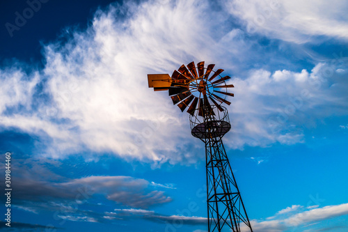 Old windmill and blue sky with clouds.