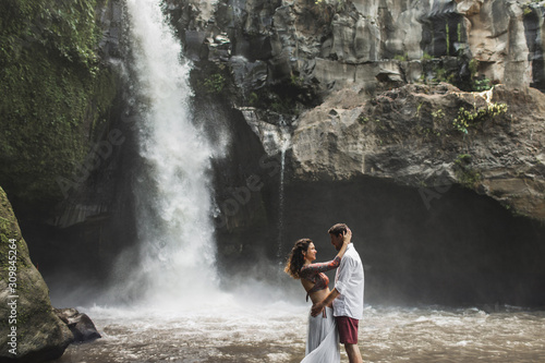 Spanish couple in love kissing with amazing view of waterfall Obraz na płótnie