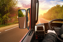 Truck Dashboard With Driver's Hand On The Steering Wheel And Side Rear-view Mirror On The Countryside Road Against Sky With Sunset