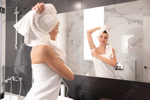 Fototapeta Young woman epilating her armpit in bathroom obraz na płótnie