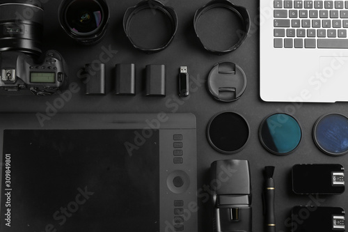 Flat lay composition with equipment for professional photographer on black background