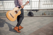 Young Guy With Guitar Walking Along The Street
