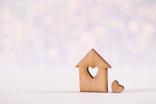 Wooden Icon Of House With Hole In Form Of Heart On Light Glitter Shiny Background With Bokeh Lights.