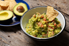 Mexican Guacamole With Tomato On Wooden Background