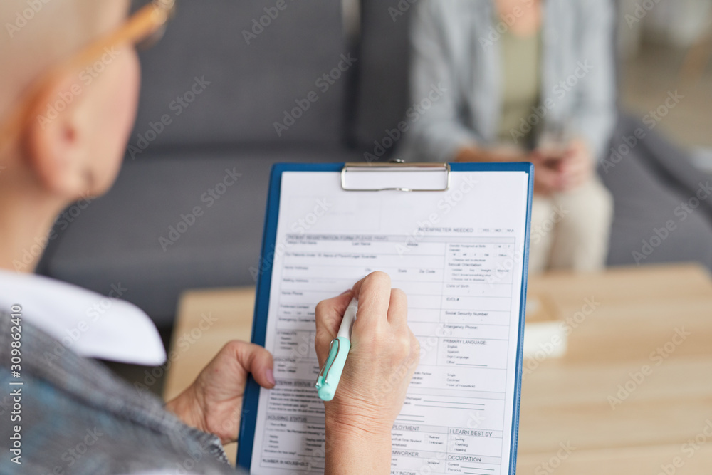 Fototapeta High angle closeup of female psychologist filling in medical form while talking to patient during therapy session, copy space